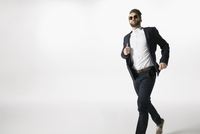 Cool businessman running against white background