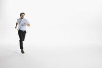 Enthusiastic businessman running against white background 11096049119| 写真素材・ストックフォト・画像・イラスト素材|アマナイメージズ