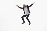 Senior businessman falling against white background 11096049193| 写真素材・ストックフォト・画像・イラスト素材|アマナイメージズ