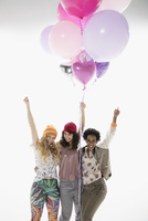 Portrait enthusiastic women friends cheering and holing multicolor balloons against white background 11096049199| 写真素材・ストックフォト・画像・イラスト素材|アマナイメージズ