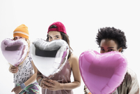 Portrait smiling women friends hiding behind heart-shape balloons against white background 11096049202| 写真素材・ストックフォト・画像・イラスト素材|アマナイメージズ