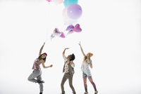 Playful women friends with multicolor balloons against white background