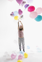 Playful woman holding bunch of multicolor balloons against white background 11096049206| 写真素材・ストックフォト・画像・イラスト素材|アマナイメージズ