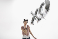 Portrait young woman with XO balloons blowing a kiss against white background