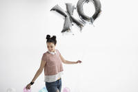 Smiling young woman with XO balloons against white background