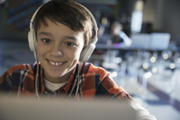 Close up smiling pre-adolescent boy wearing headphones listening to music at laptop
