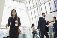 Portrait smiling businesswoman with coffee and suitcase in airport atrium 11096049654| 写真素材・ストックフォト・画像・イラスト素材|アマナイメージズ