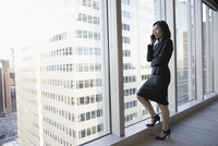 Businesswoman talking on cell phone at urban, highrise office window