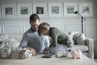 Father teaching daughter counting allowance money in living room 11096050140| 写真素材・ストックフォト・画像・イラスト素材|アマナイメージズ