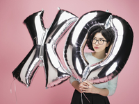 Young woman with silver XO balloons against pink background