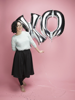 Portrait young woman holding silver XO balloons against pink background