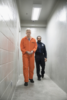 Bailiff walking prisoner in orange jumpsuit down corridor in jail 11096050481| 写真素材・ストックフォト・画像・イラスト素材|アマナイメージズ
