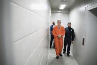 Bailiff walking prisoner in orange jumpsuit down corridor in jail 11096050483| 写真素材・ストックフォト・画像・イラスト素材|アマナイメージズ