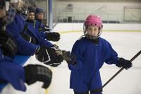 Smiling girl ice hockey player high-fiving teammates on bench 11096050521| 写真素材・ストックフォト・画像・イラスト素材|アマナイメージズ