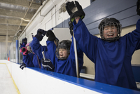Boy ice hockey players cheering from bench