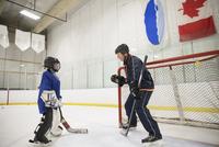 Ice hockey coach coaching boy hockey player goalie at net 11096050532| 写真素材・ストックフォト・画像・イラスト素材|アマナイメージズ