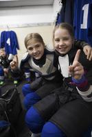 Portrait confident girl ice hockey players gesturing number 1 in locker room