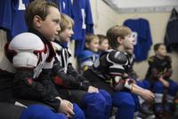 Attentive boy ice hockey players listening in locker room