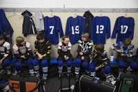 Boy ice hockey players talking in locker room