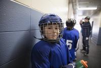 Portrait confident boy ice hockey player wearing helmet in corridor outside locker room 11096050596| 写真素材・ストックフォト・画像・イラスト素材|アマナイメージズ