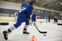 Boy ice hockey player practicing drills on ice hockey rink 11096050604| 写真素材・ストックフォト・画像・イラスト素材|アマナイメージズ