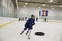 Boy ice hockey player practicing drills on ice hockey rink 11096050606| 写真素材・ストックフォト・画像・イラスト素材|アマナイメージズ
