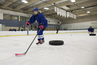 Girl ice hockey player practicing drills on ice hockey rink
