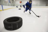 Boy ice hockey player practicing drills on ice hockey rink 11096050613| 写真素材・ストックフォト・画像・イラスト素材|アマナイメージズ