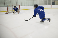 Boy ice hockey player taking a shot at goal on ice hockey rink