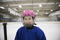 Portrait smiling girl ice hockey player wearing helmet on ice hockey rink