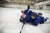 Playful boy and girl ice hockey players celebrating laying on ice hockey rink