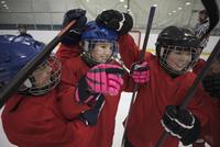 Playful boy and girl ice hockey players celebrating