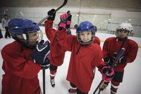 Playful boy and girl ice hockey players celebrating 11096050639| 写真素材・ストックフォト・画像・イラスト素材|アマナイメージズ