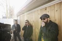 Cool music band musicians smoking cigarettes along sunny wall 11096050801| 写真素材・ストックフォト・画像・イラスト素材|アマナイメージズ