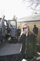 Portrait cool male music band musician smoking cigarette outside van in sunny driveway 11096050803| 写真素材・ストックフォト・画像・イラスト素材|アマナイメージズ