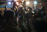 Friends with arms raised, toasting beer at party 11096050867| 写真素材・ストックフォト・画像・イラスト素材|アマナイメージズ