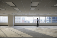 Pensive businessman looking out window in empty highrise open plan office 11096051047| 写真素材・ストックフォト・画像・イラスト素材|アマナイメージズ