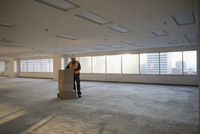 Construction worker with cardboard boxes in sunny empty, unfinished highrise office 11096051074| 写真素材・ストックフォト・画像・イラスト素材|アマナイメージズ
