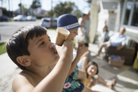Boy eating melting ice cream cone on summer beach house porch 11096051147| 写真素材・ストックフォト・画像・イラスト素材|アマナイメージズ