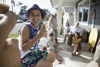 Smiling boy eating ice cream cone with family on summer beach house porch 11096051148| 写真素材・ストックフォト・画像・イラスト素材|アマナイメージズ