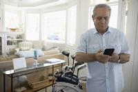Senior man with golf clubs using smart phone in beach house 11096051200| 写真素材・ストックフォト・画像・イラスト素材|アマナイメージズ