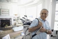 Smiling senior man carrying golf clubs in beach house 11096051202| 写真素材・ストックフォト・画像・イラスト素材|アマナイメージズ
