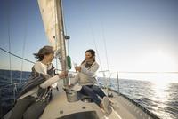 Women friends toasting champagne flutes on sunny sailboat 11096051436| 写真素材・ストックフォト・画像・イラスト素材|アマナイメージズ