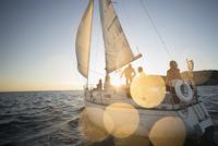 Friends sailing on sunset sailboat 11096051444| 写真素材・ストックフォト・画像・イラスト素材|アマナイメージズ
