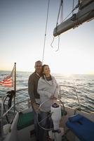 Serene affectionate couple at helm of sunset sailboat 11096051449| 写真素材・ストックフォト・画像・イラスト素材|アマナイメージズ