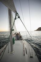 Friends relaxing on sunset sailboat 11096051454| 写真素材・ストックフォト・画像・イラスト素材|アマナイメージズ