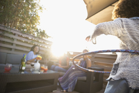 Mother watching daughter using plastic hoop on sunny deck 11096051866| 写真素材・ストックフォト・画像・イラスト素材|アマナイメージズ