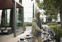 African American businessman using ride share bicycle outside office building 11096052010| 写真素材・ストックフォト・画像・イラスト素材|アマナイメージズ