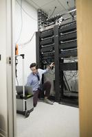 Focused technician with laptop working at server panel in server room 11096052096| 写真素材・ストックフォト・画像・イラスト素材|アマナイメージズ