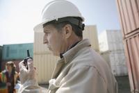 Serious Caucasian foreman using walkie-talkie in industrial container yard 11096052690| 写真素材・ストックフォト・画像・イラスト素材|アマナイメージズ